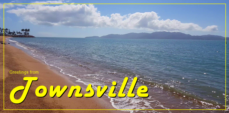 Townsville postcard featuring waves lapping on a beach and Magnetic island in the background